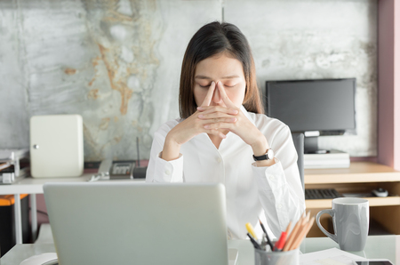 Young business people are suffering from headaches,Asian women Stressful Working with a notebook for a long time,Office syndrome concept