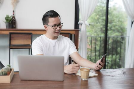 Asian man using smartphone and notebook in cafe Stockfoto