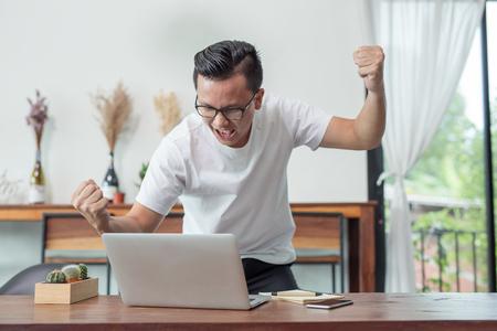 Happy businessman raising hands looking at laptop,Concept achieving goal business success