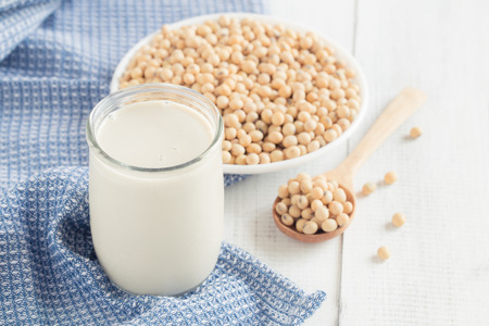 A glass of soy milk on a white wood floor with soybean as a background.