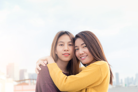 Couple of young asian women on top of building with happiness moment, lesbian couple concept