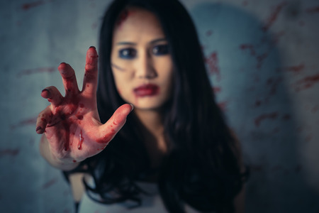 Asian woman's hands are bloody red in dark background, Concept of murder and crime