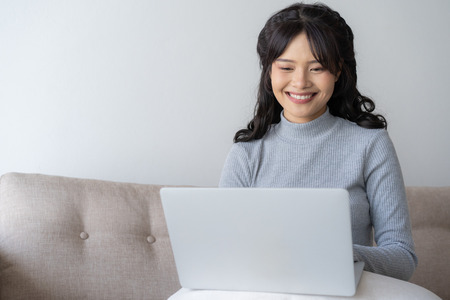 Asian women using laptop at home,Asian girl sitting and smiling working at home