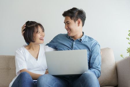 Asian young couple make fun of working on laptop. they sit on sofa in the contemporary living room.