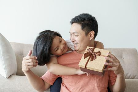 リビングルームで娘のためのギフトボックスを与えるアジアの父。かわいい女の子とソファに座っている父親は家で幸せになる