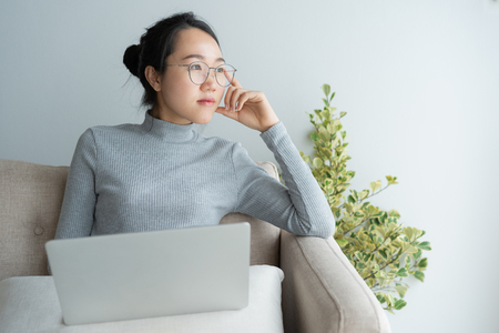 Young asian woman working on laptop in the home . And sit at table resting chin on hand