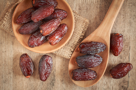 close up picture of dates palm fruit in cup and spoon on wooden table background. Dates palm fruit dry is snack healthy.