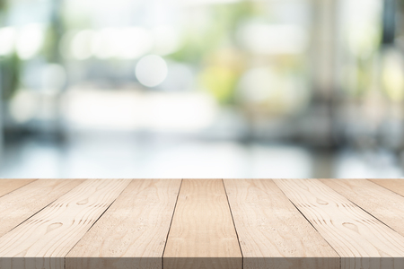 Empty brown wood table top on blur background at shopping mall, copy space for montage you product Standard-Bild