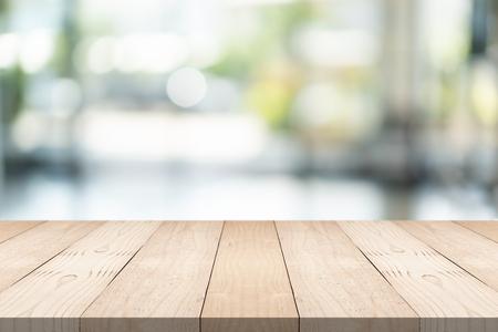 Piano del tavolo in legno marrone vuoto su sfondo sfocato al centro commerciale, copia spazio per il montaggio del prodotto