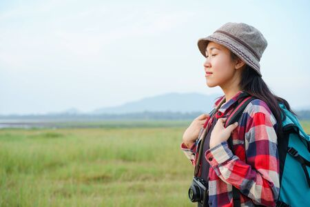 Asian women are closing their eyes and enjoying nature on the mountains and sky background. A young girl is traveling on summer vacation. Stok Fotoğraf
