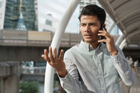 Portrait of asian young businessman standing at Outside Office. A man wear shirt so smart and talking on  smartphone to business conversation. Stok Fotoğraf