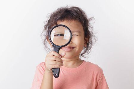 Asian little girl holding magnifying glass smiling. A Little cute child girl looking magnifying glass on white background. Stok Fotoğraf - 124531130