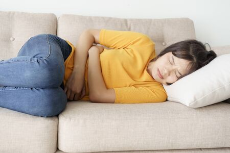 asian woman with menstruation and pain period cramps. young women having painful stomachache. Stok Fotoğraf - 124531135