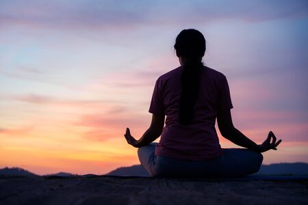 asian  woman sit  lotus yoga position at sunset . Practicing yoga makes meditation for healthy breathing  and relaxation
