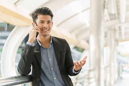 Portrait of asian young businessman standing at Outside Office. A man wear suit so smart and talking on  smartphone to business conversation.