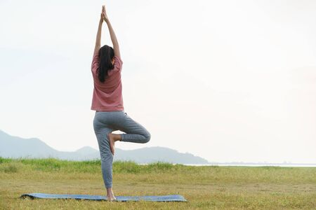 Asian young woman exercise and practice yoga in the relax nature background.