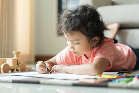 Cute little asian girl drawing homework and writing with color Wax crayons on paper in her home