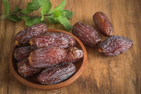 close up picture of dates palm fruit in cup and mint on wooden table background. Dates palm fruit dry is snack healthy. Stok Fotoğraf - 128696273