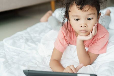Asian girl are watching video that are exciting on online media. The little girl use the tablet to watch video for home entertainment.