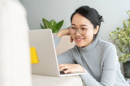 Asian woman is working on a laptop in home. On her face are smile when she work at sofa.