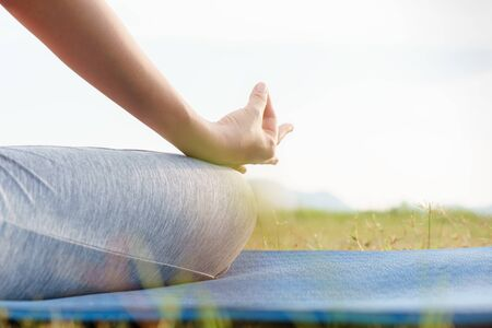 close up hand and half body of health woman sit in lotus yoga position in the morning at park. Practicing yoga makes meditation for healthy breathing  and relaxation Stok Fotoğraf - 128696339