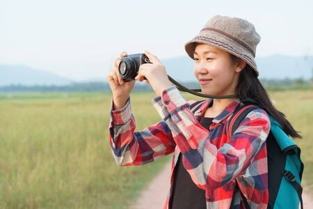 Asian tourist woman taking photo by digital camera on nature mountain view. A young girl is traveling on summer vacation.