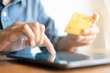 Close up hand of businessmen are buying online with a credit card. Men are using tablet and doing online transactions.