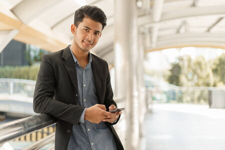 Portrait of asian young businessman standing at Outside Office. Young businessman wear suit smiling and looking at camera.