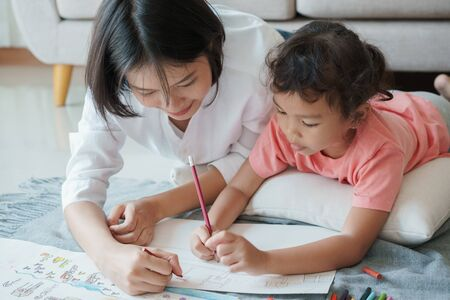 Asian family with mother and daughters are drawing on paper at home. Parents are teaching girl to draw with colors on white paper. Self Study concept at home Stok Fotoğraf