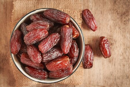 close up picture of dates palm fruit in cup on sackcloth, wooden table background. Dates palm fruit dry is snack healthy.