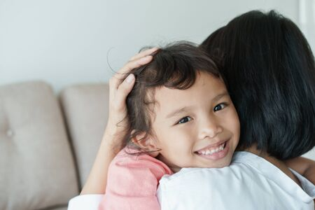 Asian families with daughters and mothers are embracing each other with love. Asian girl with a smile on her face is in the mothers arms. Family with mother and girl who have shown love to each other by embracing Stok Fotoğraf