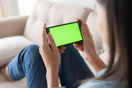 Close up  asian woman hand touching smartphone  screen green on sofa in living room at home Stok Fotoğraf - 128696570