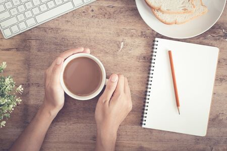 Top view of business hand on desk have coffee, toast, notebook blank  and pencil  on   wooden table background. Picture of the home office concept. Stok Fotoğraf