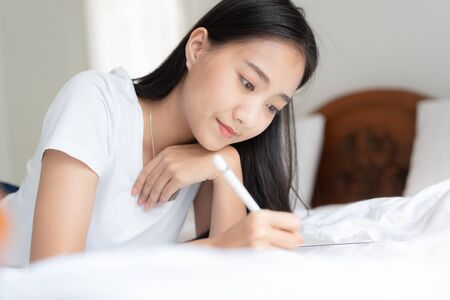 Beautiful Asian woman is drawing on the bed. Asian girl using tablet to learn to draw at her home.