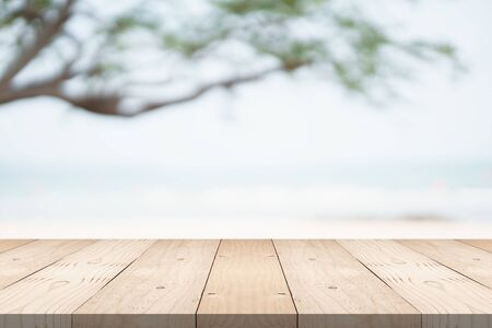Empty wood table top on green background at the beach