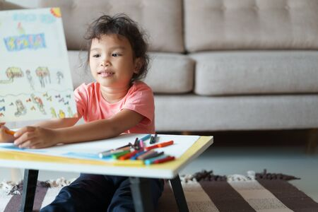 Cute little asian girl Sitting holding a drawing paper, drawing homework and writing with color Wax crayons on paper at living room