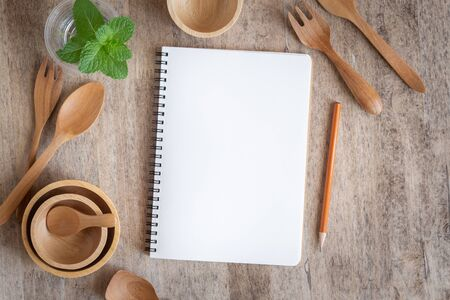 Blank notebook for text note on wooden table background. On wooden have spoon fork and pencil Stok Fotoğraf