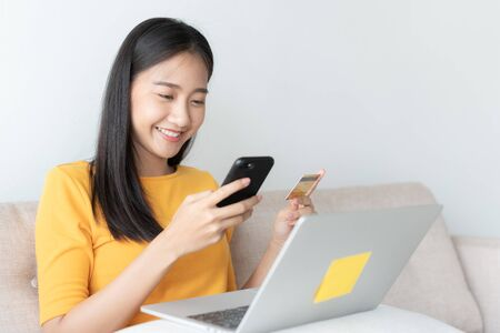 portrait of Beautiful young Asian women are buying  online with a credit card. asia girl are using smartphone and making online transactions in the living room at home.