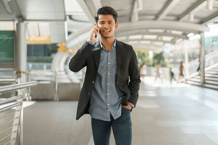 Portrait of young businessman standing at Outside Office and talking on  smartphone. Asian Business man wear suit and handsome look.