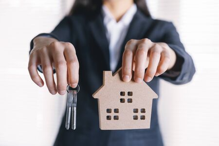 hand of Asian business woman are holding key and model houses.