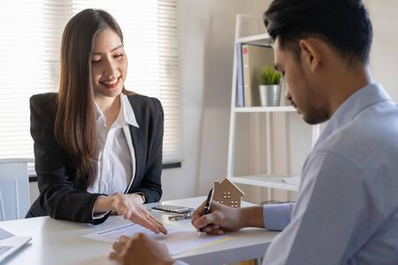 Salesmen are letting the male customers sign the sales contract, Asian women and men are doing business in the office, Business concept and contract signing Stok Fotoğraf - 128696893