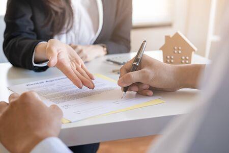 Verkäufer lassen die männlichen Kunden den Kaufvertrag unterschreiben, asiatische Frauen und Männer machen Geschäfte im Büro, Geschäftskonzept und Vertragsunterzeichnung