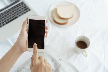 Hands of working woman holding and using smart phone on desk background. On the desk have cup coffee, breads and laptop. Stok Fotoğraf - 128697042