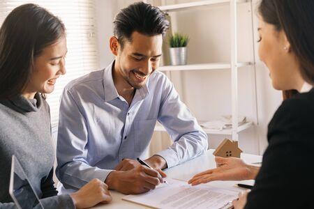 Verkäufer lassen die männlichen Kunden den Kaufvertrag unterschreiben, asiatische Frauen und Paare machen Geschäfte im Büro, Geschäftskonzept und