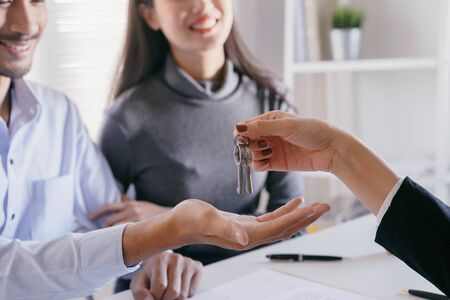 hand of Salespeople give keys to couples who are customer. Men are doing business in the office, business concept. Stok Fotoğraf - 128696995