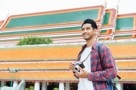 Asian man tourist walking talk smart phone and smile at Wat Suthat Thepwararam Ratchaworawihan Bangkok, Thailand in the summer time, Solo travel and backpacker concept