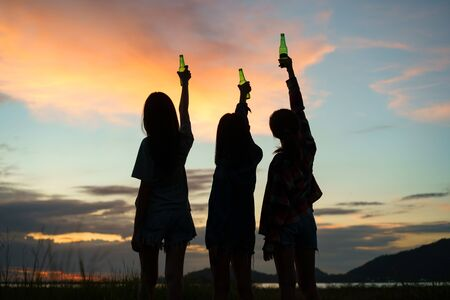 group teen women asian holding beer from bottles in the midst of nature. While standing back when the sunset.