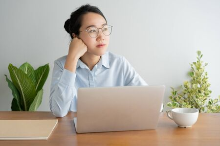 Young asian woman working on laptop in the home office desk. And sit at table resting chin on hand. Stok Fotoğraf - 128697099