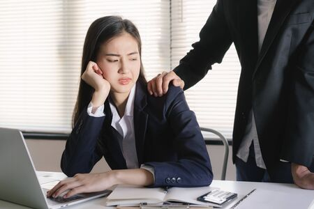 Asian women sexual harassment at working in the office Manager putting his hand on the shoulder of his Stok Fotoğraf - 128697160