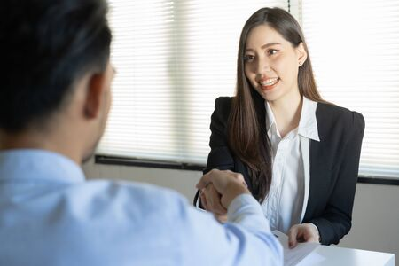 Salesman shaking hand with male customers in her office in the home trading agreement. Asian women and man smile happiness